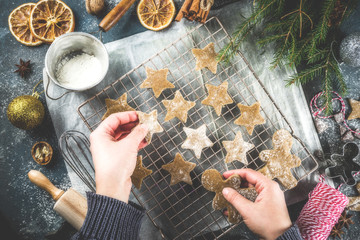 Girl cooking christmas homemade gingerbread star cookies, gingerbread men, flat lay, top view, with accessories ingredients for baking. Dark blue concrete background, copy space, hands in picture