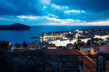 Dubrovnik aerial night view on old town and port after sunset with illuminated fortress wall and dramatic cloudscape, Croatia
