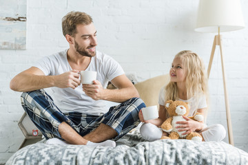 happy father and daughter holding tea cups and smiling each other on bed