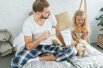 father holding cup of coffee and looking at little daughter with tasty croissants on plate