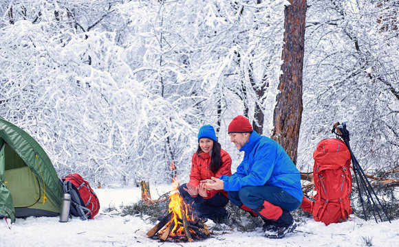 Winter camping in the forest with a tent and a fire.