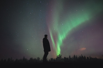 man standing and watching Northern light / Aurora borealis in the sky of finland during winter