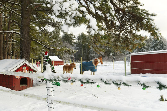 A wooden fence on a farm decorated with New Year's Christmas toys and garlands. USA. Maine.
