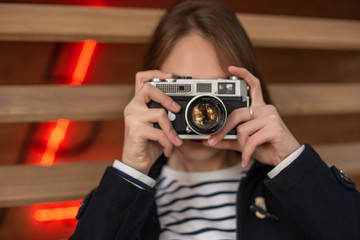 Happy young hipster woman holds retro photo camera