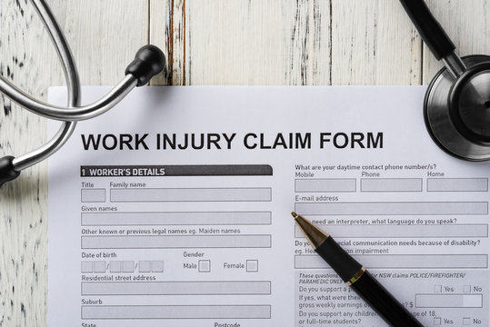 top view work injury claim form with stethoscope  and box of pills medical and insurance concept