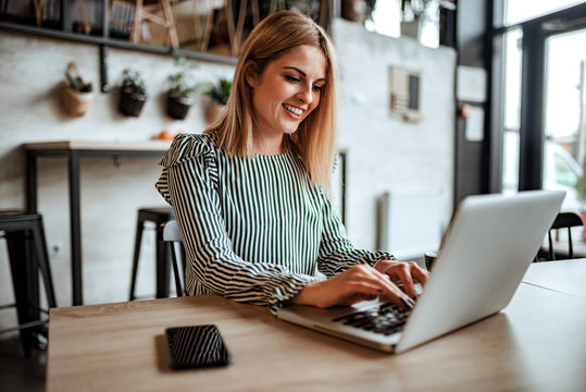 Smiling woman typing on laptop indoors.