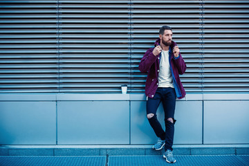 Handsome young man in purple winter jacket drinking coffee. The guy drinking coffee on the street.