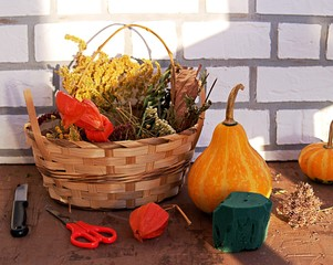Materials for creating autumn floral compositions: decorative pumpkins, dried flowers and herbs in a wooden basket, floral sponge, scissors, knife.