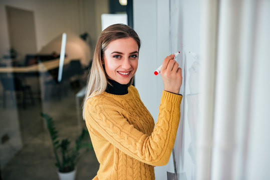 Portrait of a happy young businesswoman  writing on white board.