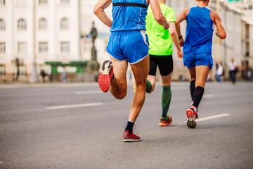 back three male runners running marathon in city
