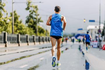 Wall Mural - back man runner running city street on wet road