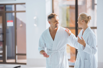adult smiling couple  in white bathrobes walking and talking in spa