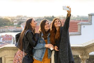 Young trendy women taking selfie on street