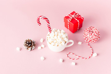 White mug with marshmallows Candy Cane, red gift box, pine cone, decorative lace on pink background Flat Lay Winter traditional drink food Festive decor. Christmas New Year presents Xmas holiday