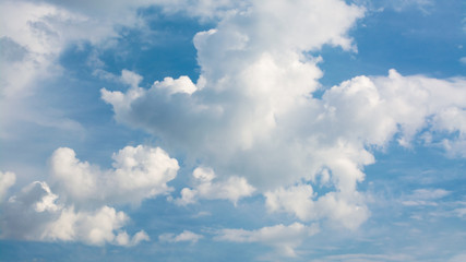 White curly clouds in a blue sky. Sky background