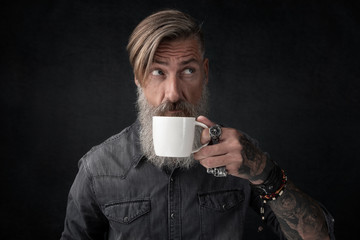 Porträt eines attraktiven bärtigen Mannes, der sein Kaffee trinkt. Freigestellt vor einem dunklen Hintergrund