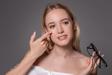 Young blonde woman holding contact lens on finger in front of her face and holding in her other hand a black glasses on gray background.