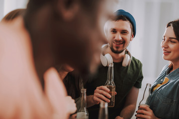 Portrait of smiling young man with headphones holding bottle of beer while standing near joyful girl