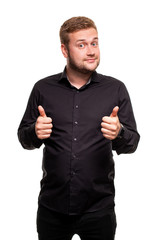 Image of young attractive man dressed in black shirt standing over white background looking at camera and showing thumbs up gesture.