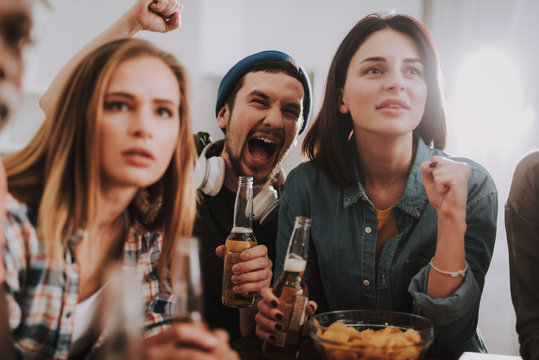 Happy bearded man in hat exulting and screaming with joy while two charming girls supporting their favorite team. Friends holding bottles of beer