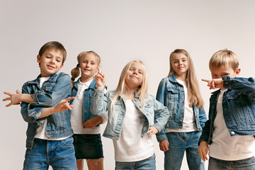 The portrait of cute little kids boy and girls in stylish jeans clothes looking at camera against white studio wall. Kids fashion and happy emotions concept Wall mural