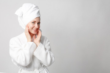 Beautiful girl wearing white bathrobe with towel on the head, looking at camera and smiling, a model with light nude make-up, white studio background, beauty photo, copy space.