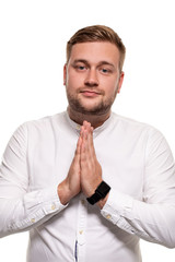 Office worker keeps palm together in please gesture. Bearded man wishing and looking at camera. Isolated on white.