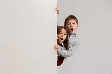 Banner with a surprised children peeking at the edge with copyspace. The portrait of cute little kids boy and girls looking at camera against white studio wall. Kids fashion and happy emotions concept