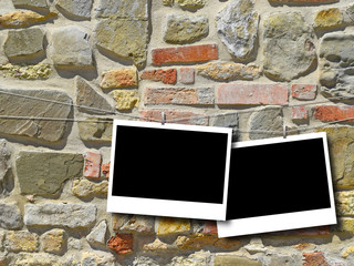 Two blank rectangular instant photo frames on multicolored stone wall background