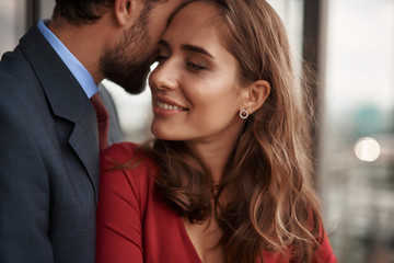 Concept of romantic date. Close up portrait of happy beloved lady clinging with love to her male lover while standing in his arms on balcony