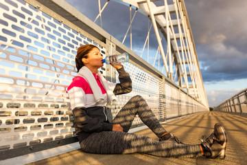 Portrait of woman taking break from jogging,drinking water