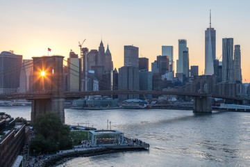 New York City - Rays of sunlight shine through the arches of the Brooklyn Bridge with the downtown Manhattan skyline in the background