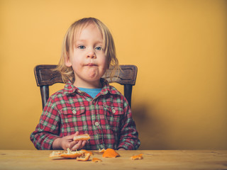 Toddler eating a clementine