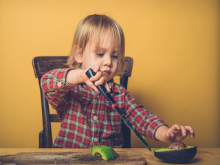 Little toddler cutting avocado at table