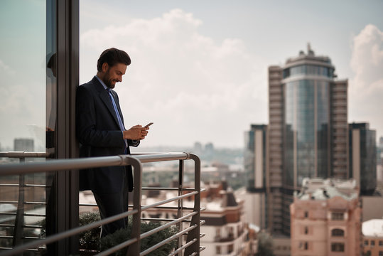 Take a pause. Full length portrait of smiling businessman reading massages on smartphone while standing on office terrace. Copy space on right