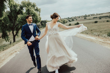 Wedding couple running on the road.Happy young bride and elegant groom running away holding hands.Stylish couple of newlyweds on their wedding day.