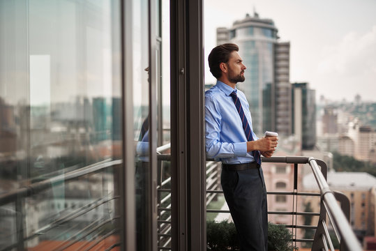 Corporate time-out culture. Side on portrait of businessman standing on office balcony with cup of coffee and looking at city view