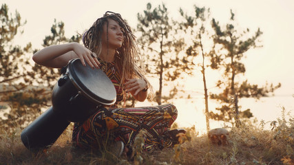 Beautiful young hippie woman with dreadlocks playing on djembe. Funky woman drumming in nature on an ethnic drum at sunset or sunrise