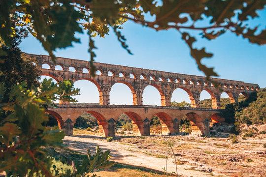 Pont du Gard Bridge on the Gardon River near Avignon - view of the bridge through tree branches in early autumn