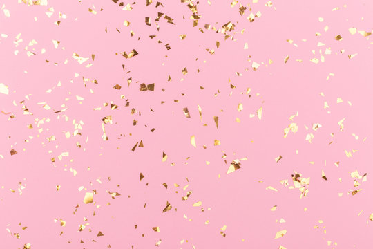 Golden sparkles on pink pastel trendy background. Festive backdrop for your projects.