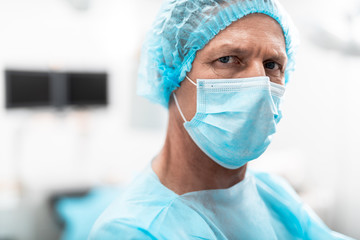 Portrait of medical worker in blue uniform and a medical mask on his face thoughtfully looking