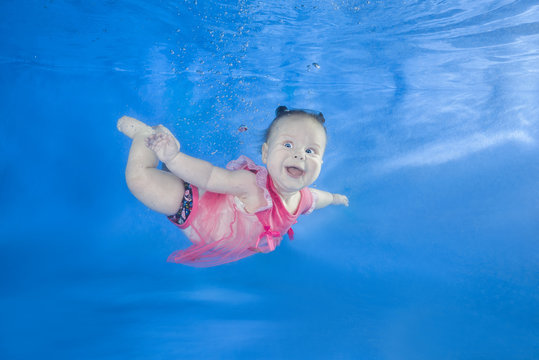 Little baby in pink dress swim underwater. Baby swimming underwater in the pool on a blue water background. Healthy family lifestyle and children water sports activity.