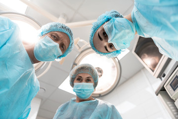Bottom view of three professional doctors in medical clothes leaning to their patient and frowning