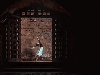 Young ballerina dancing near brick wall