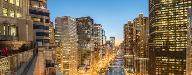 Panoramic illuminated waterfront skyscrapers along Chicago river at blue hour