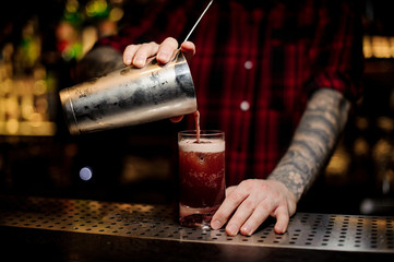 Tattooed barman pouring sweet juicy cocktail into a glass on bar