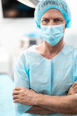 Vertical waist up portrait of confident surgeon in protective mask looking at camera with serious expression