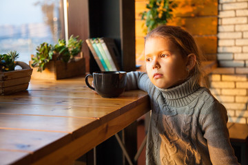 Little girl dreaming with a cup of tea