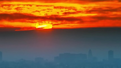 Fototapete - Sunrise sun rising from foggy clouds above city of Los Angeles skyline. 4K UHD Timelapse.