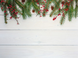 Christmas background, fir branches and berberis branches with red fruit and star anise on white wooden background